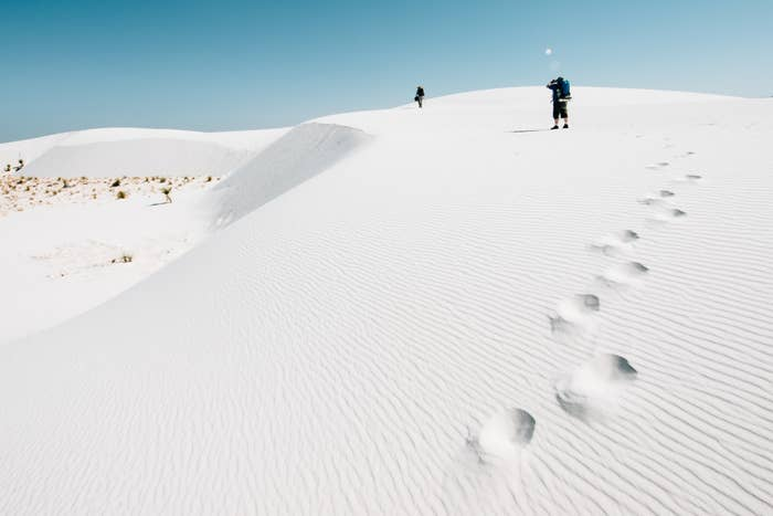 People hiking on white sand in giant dunes