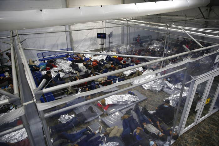 An overhead view shows dozens of people in a small room, many of them lying under emergency blankets