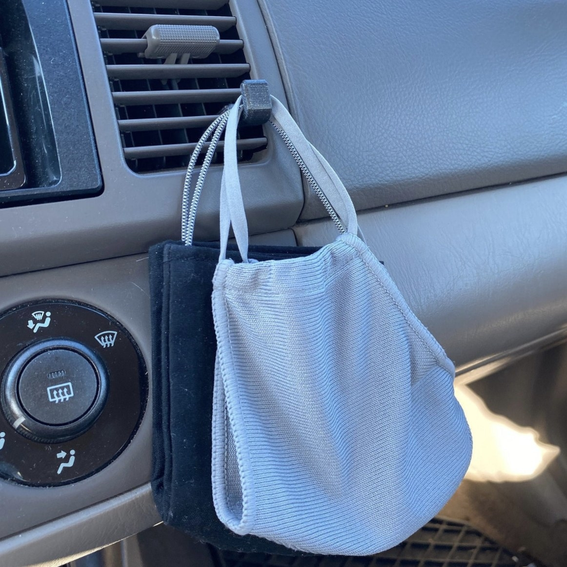 A hook attachment on a car vent holding face masks