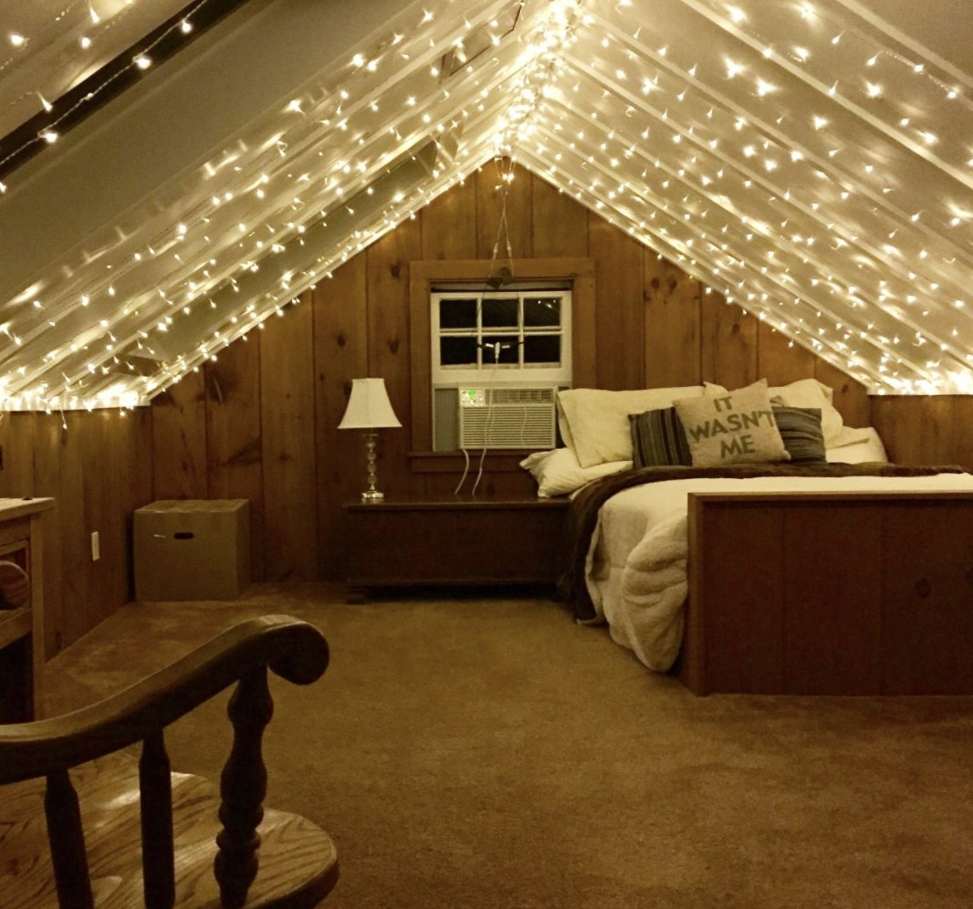 A bedroom with fairy lights on the ceiling