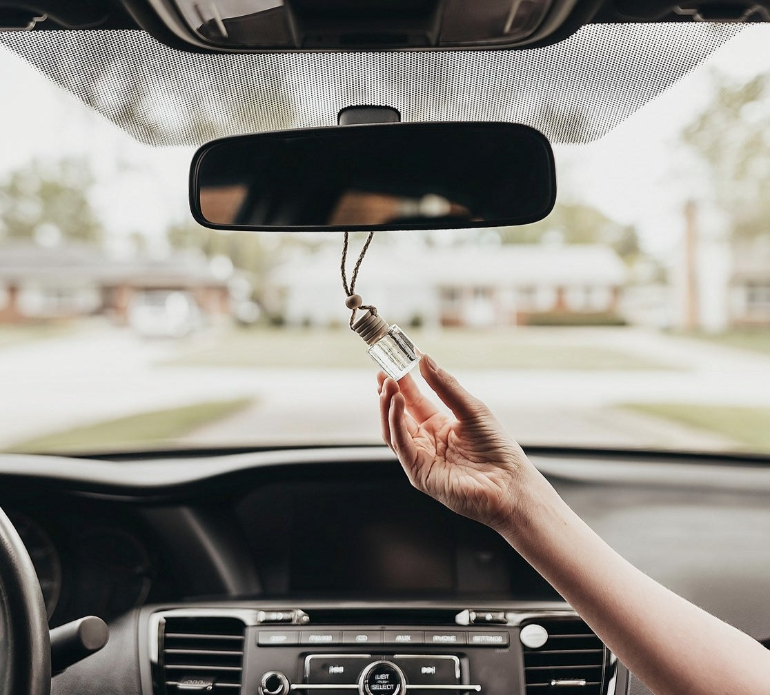 A person holding a diffuser handing on a rear view mirror
