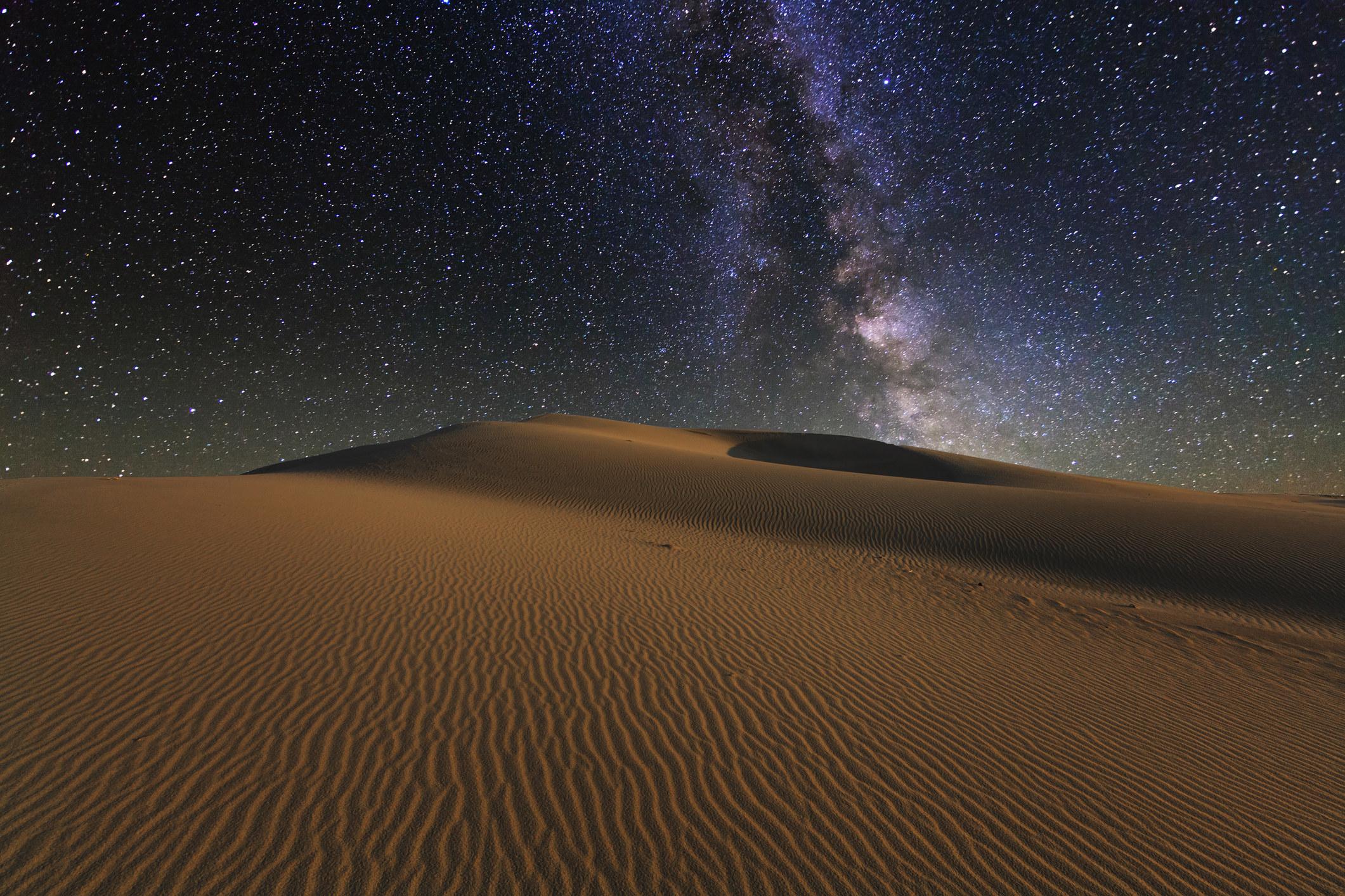 Starry night sky above open wind-swept desert