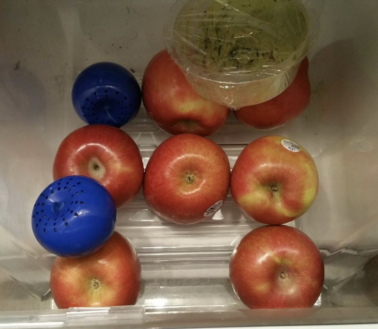 Produce balls in a drawer with apples