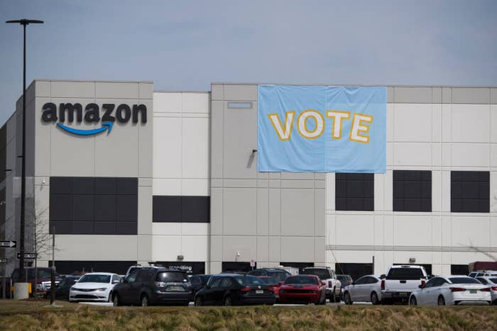 """A giant flag that reads """"Vote"""" hangs over the side of a building beside the Amazon logo"""