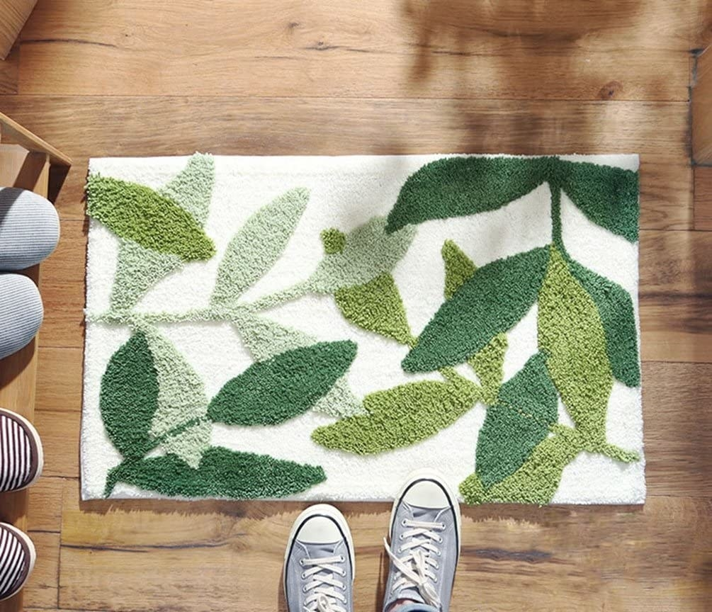 Model stepping in front of doormat with leaf pattern