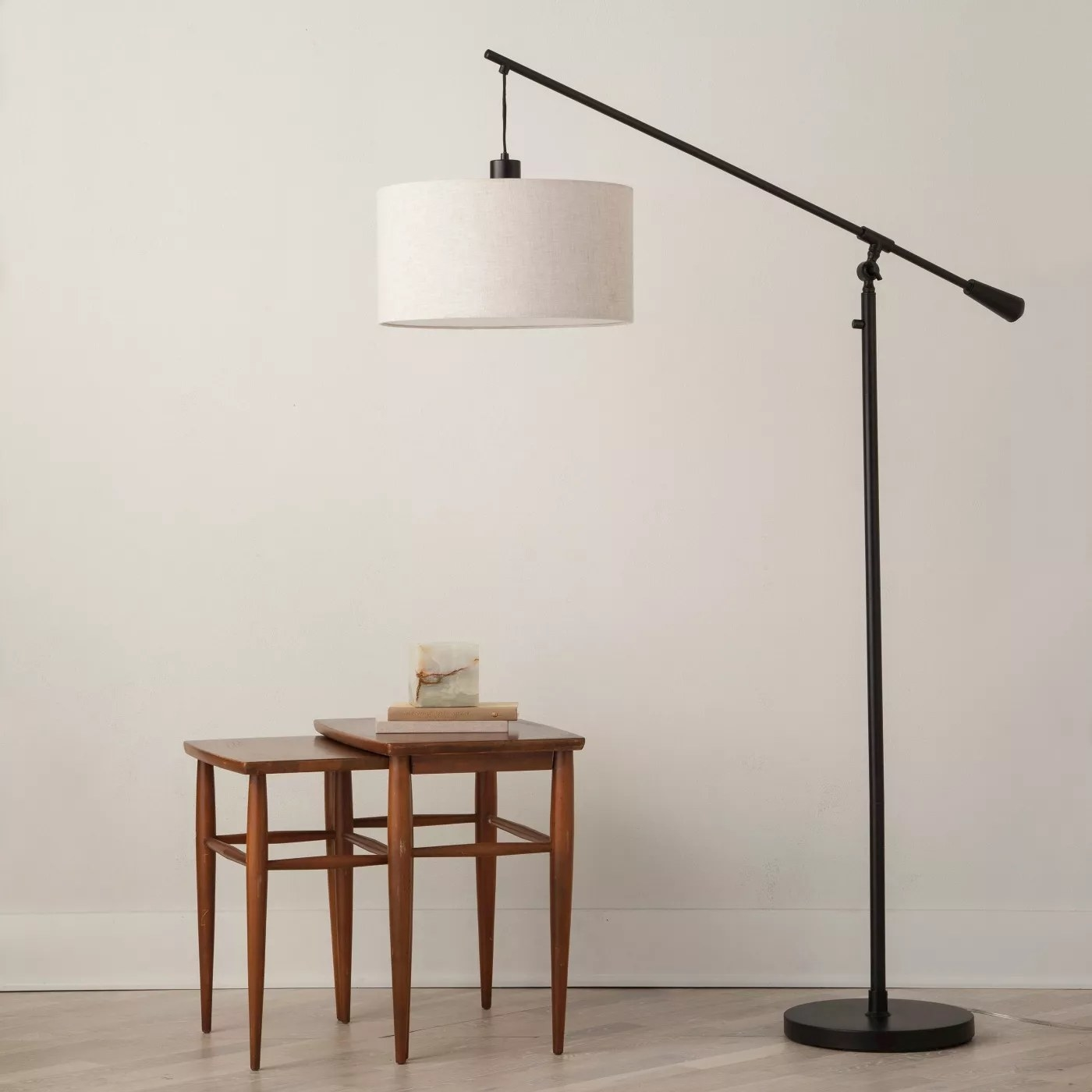 The pendant floor lamp with a black base and white lamp shade in a living room