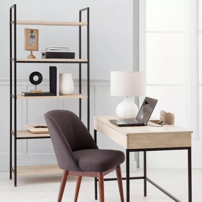 The small wooden writing desk with metal legs and a charging port in a home office