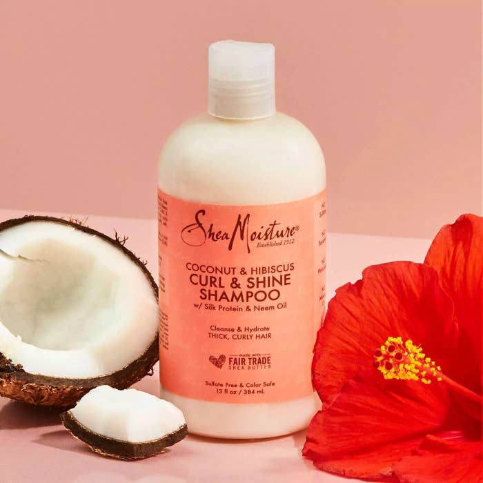 The white shampoo in a round bottle with a pink label