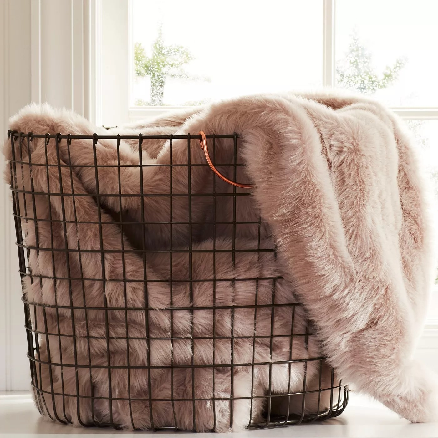 The black wire storage basket with copper handles holding some blankets