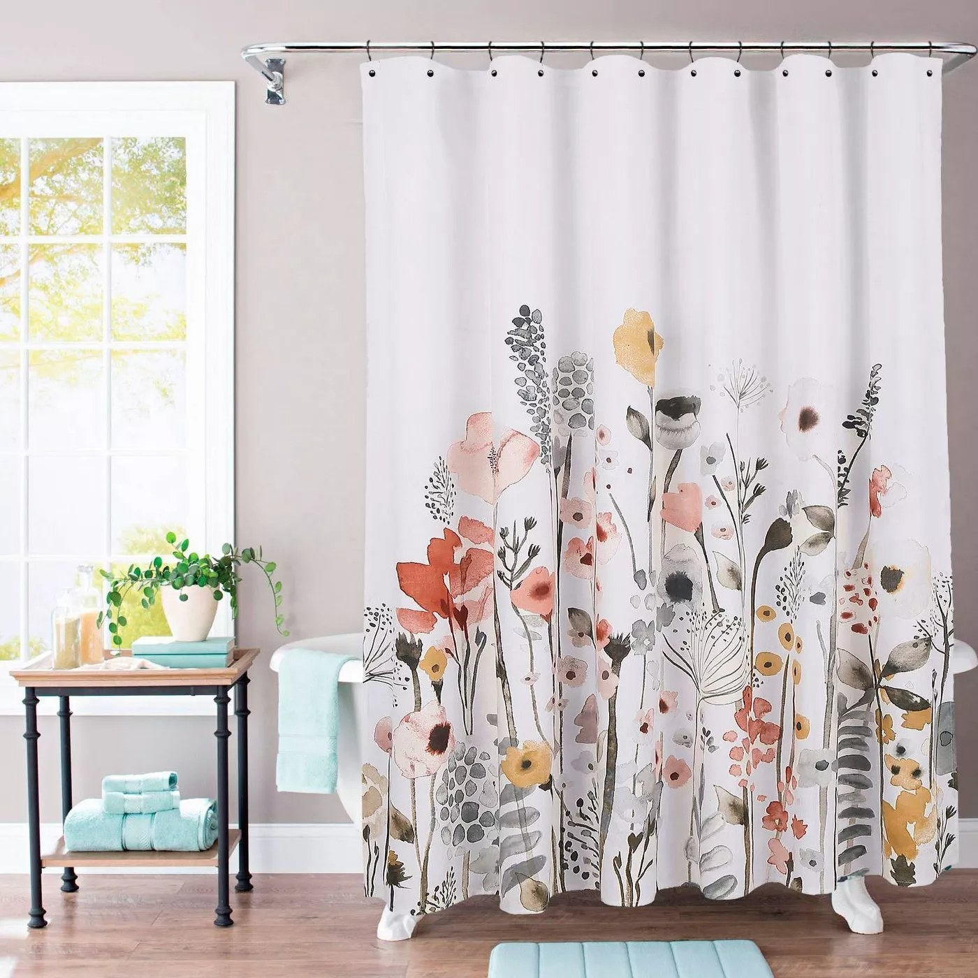 The floral shower curtain with a white background on a shower in a bathroom