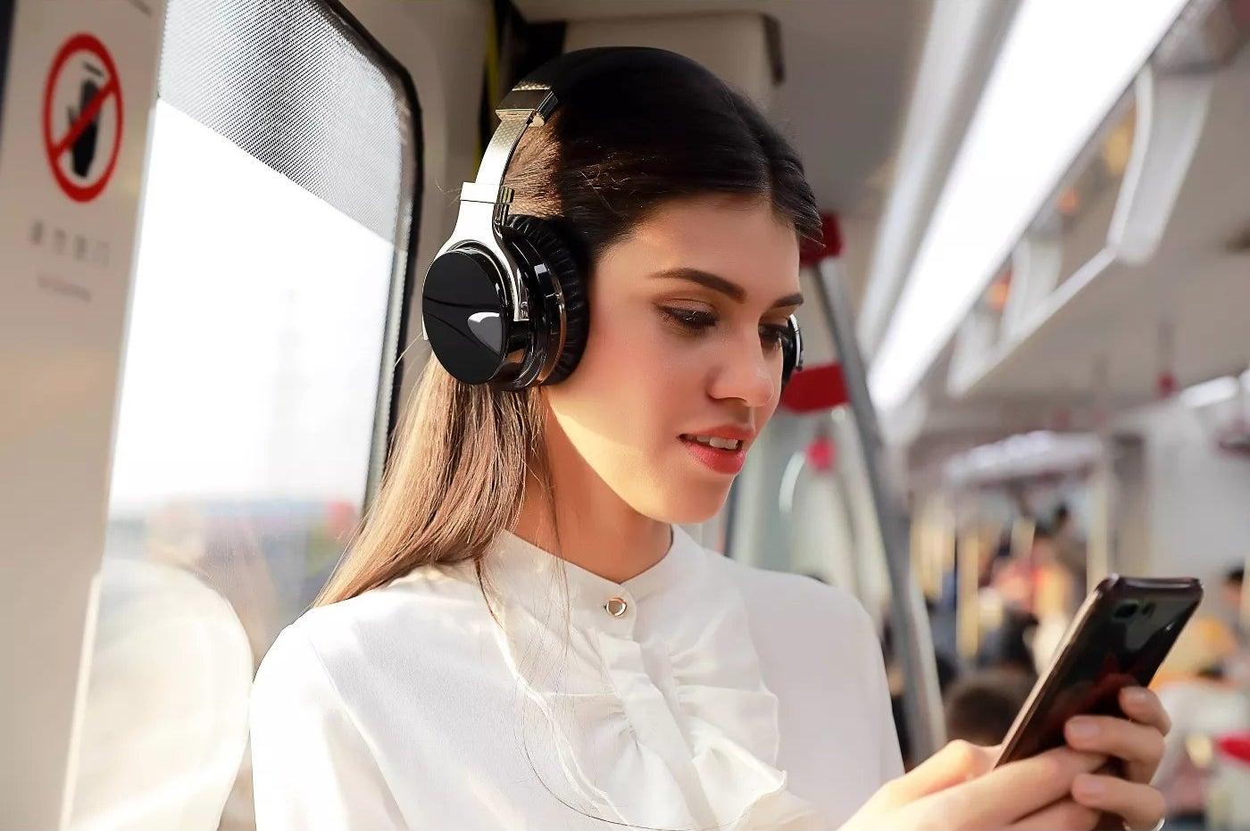 A model wearing the headphones on public transportation