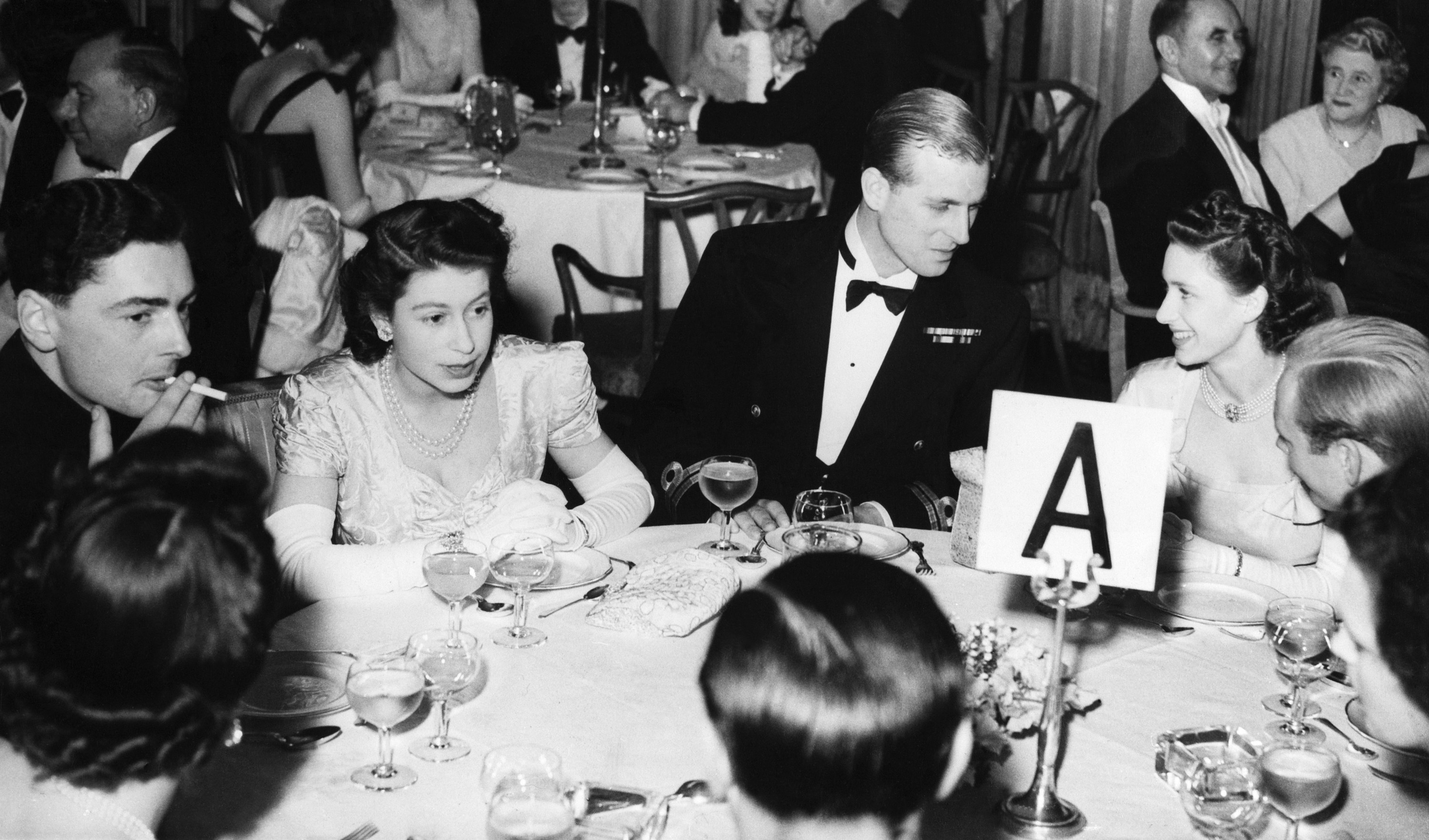 The Queen and the duke at a table at a dinner party with other guests