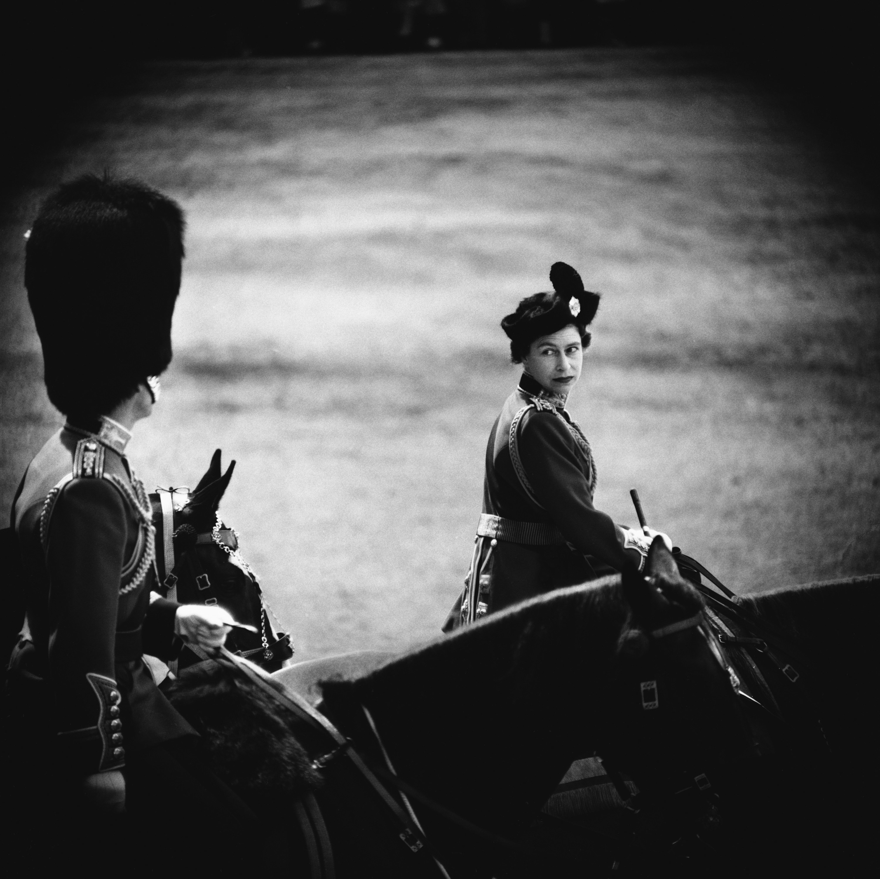 The queen looks back from horseback towards her husband, who is seen from behind