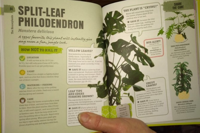 A reader holds the book open to a page describing how to care for a split-leaf philodendron