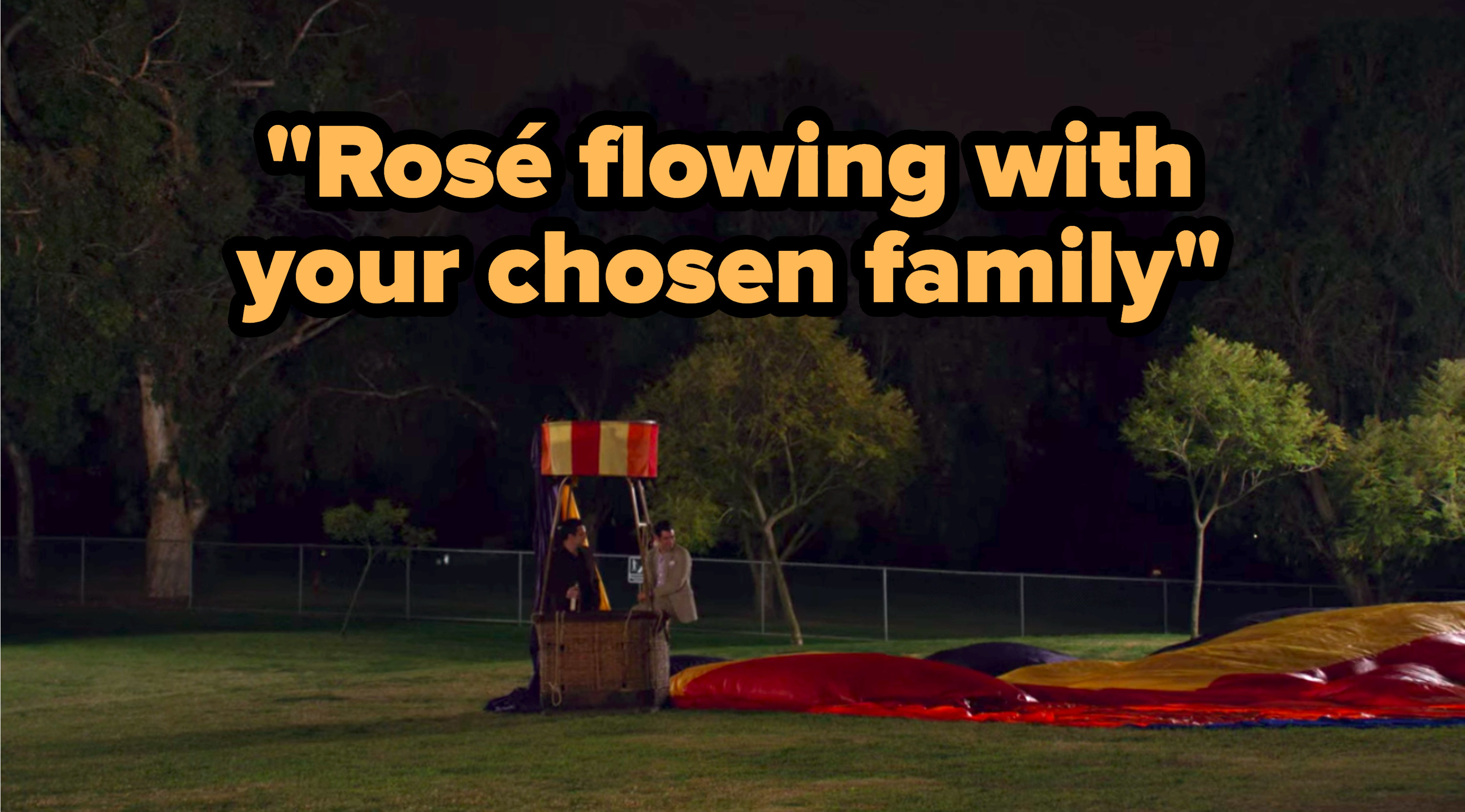 """""""Rosé flowing with your chosen family"""" written over Nick and Schmidt from """"New Girl"""" standing in a grounded, deflated hot air balloon"""