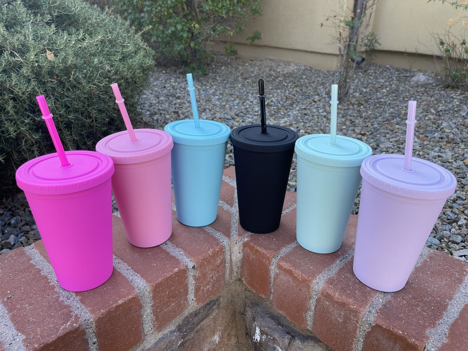 six different colored pastel tumblers lined up on a brick ledge