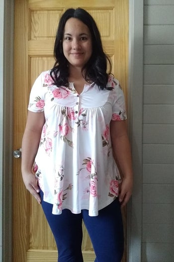 reviewer wearing the tunic in pink floral print