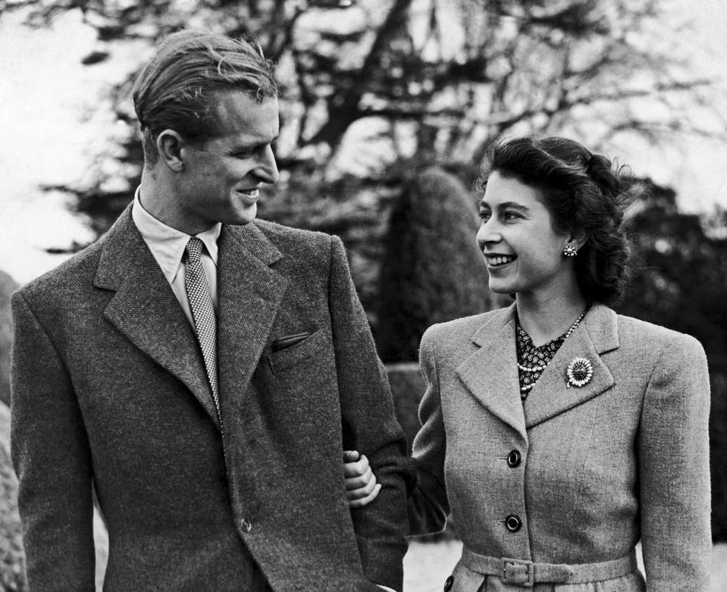 A young Prince Philip and Queen Elizabeth walk arm in arm