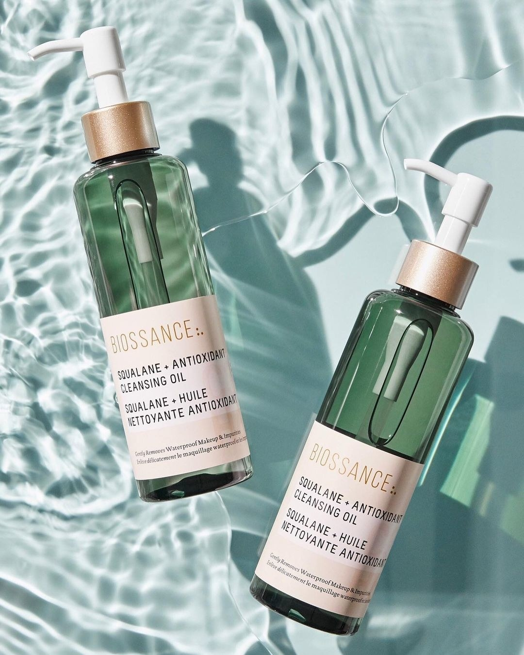 Two bottles of cleansing oil floating in water