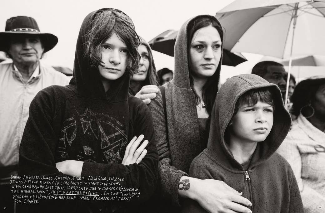 A woman with a black eye and two children stand in a crowd