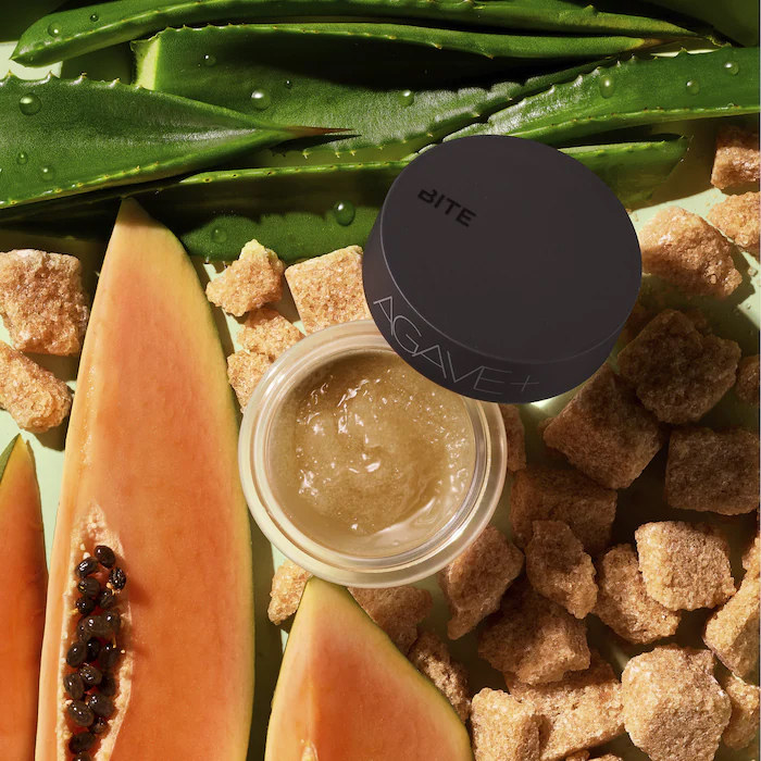 An open container of lip scrub with aloe sugar cubes and fruit surrounding it