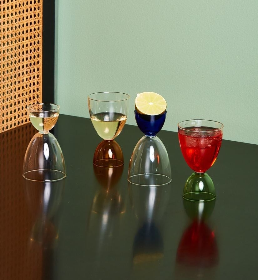 Four cocktail glasses; two being used as shot glasses and the other two as cocktail glasses