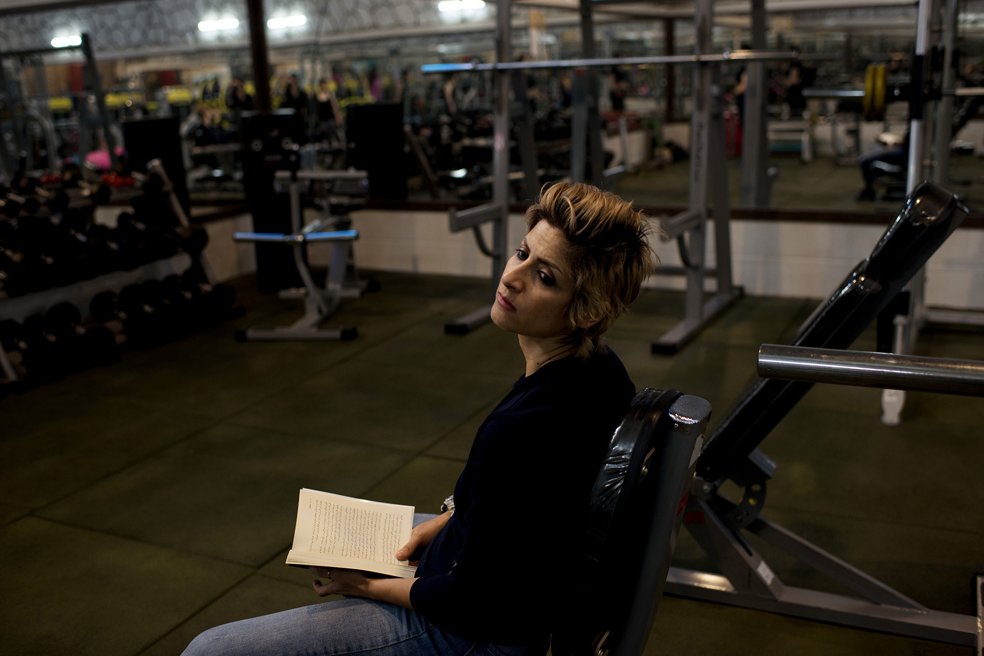 A woman with a short hair cut reading a book while sitting in a gym