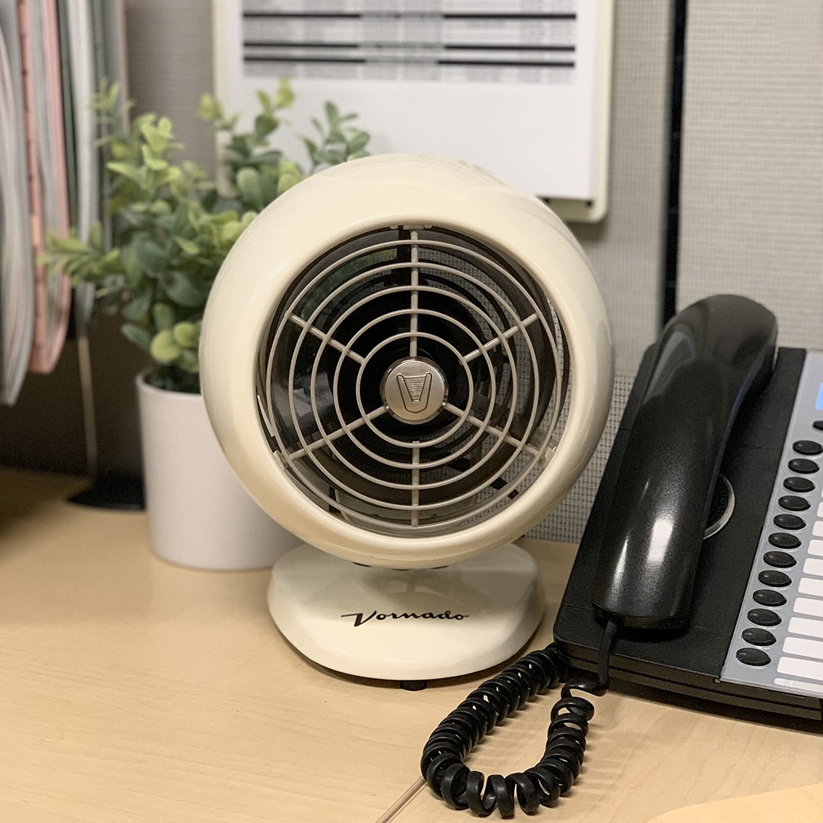 reviewer image of the vintage white vornado personal fan with a classic base on a desk next to an office phone