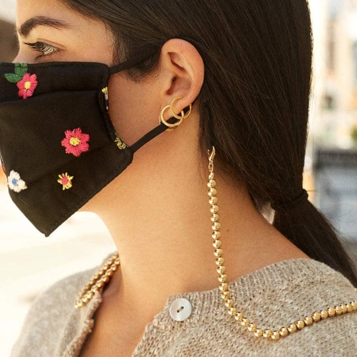 side view of a different model wearing the gold chain attached to a face mask
