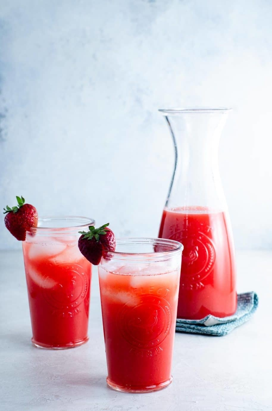 A carafe and two glasses of strawberry agua fresca