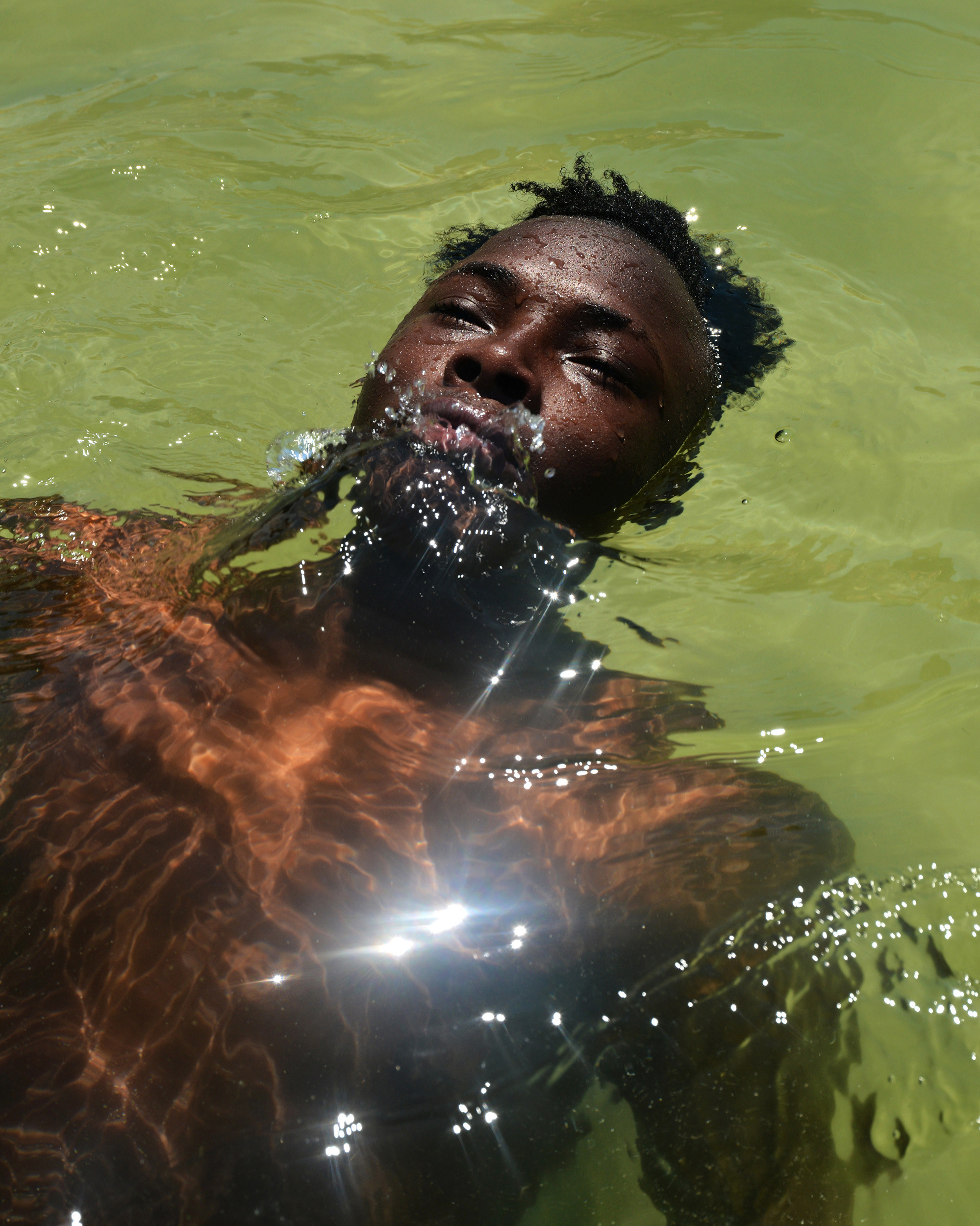 A man is floating in water with sunlight