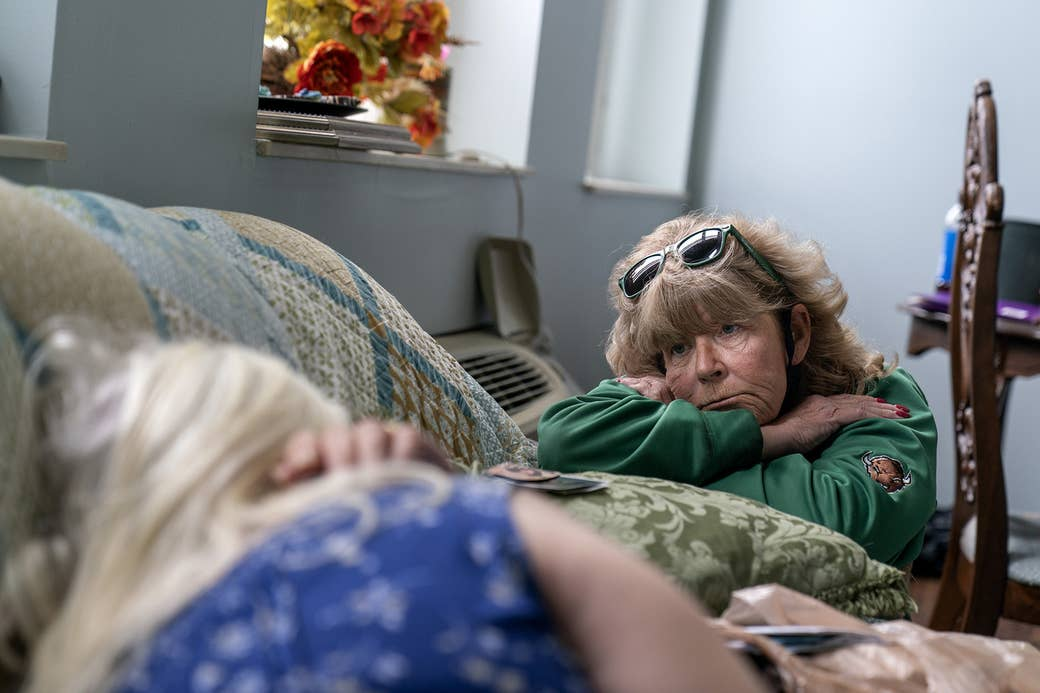 An older woman with her head in her arms talks to a woman in bed