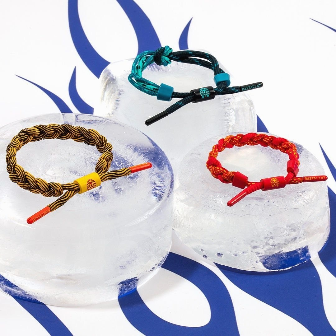 three different colored woven bracelets on ice
