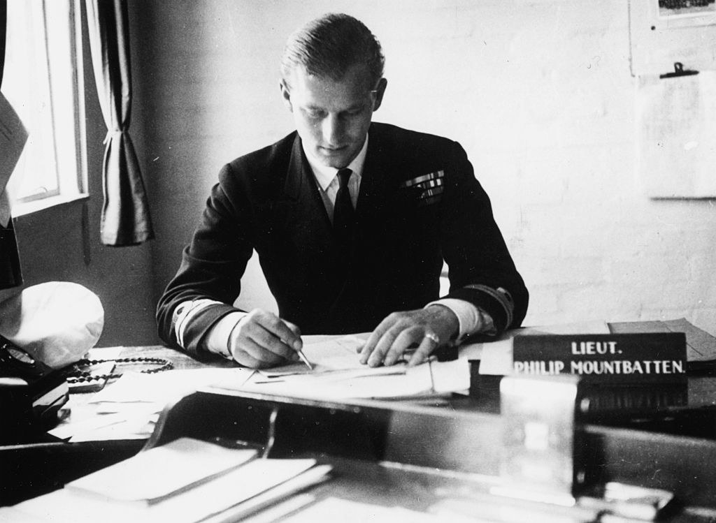 Prince Philip sitting at a desk in his military uniform
