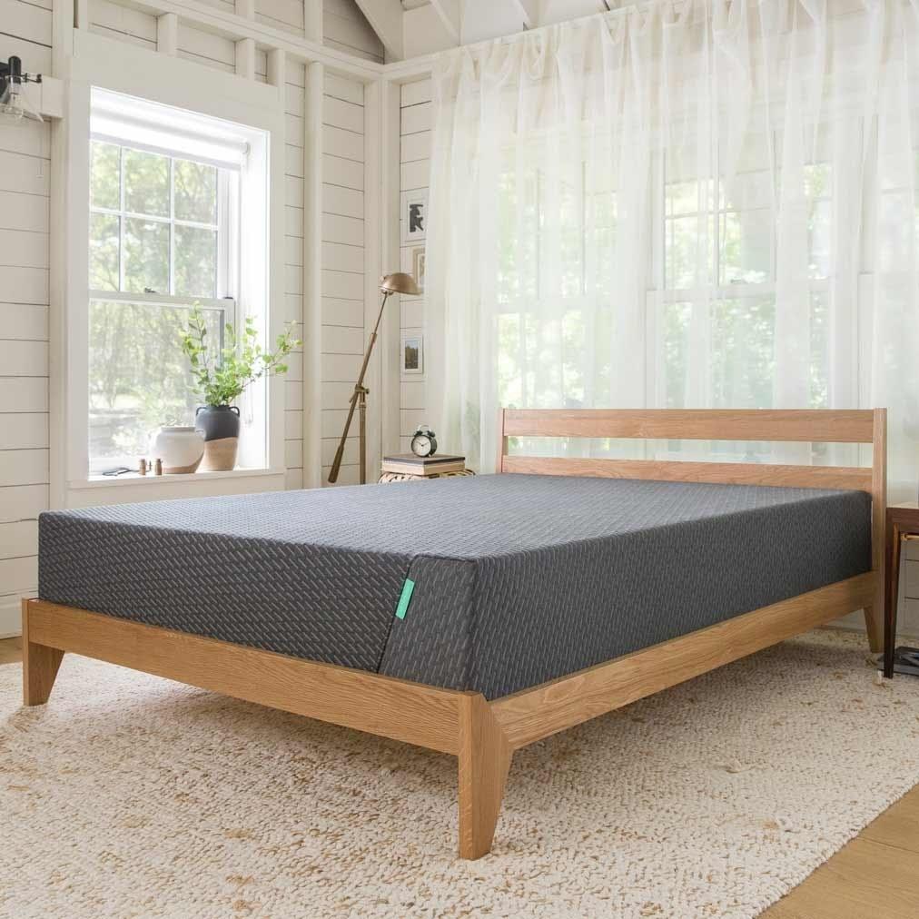 a gray mattress on a wooden bed frame