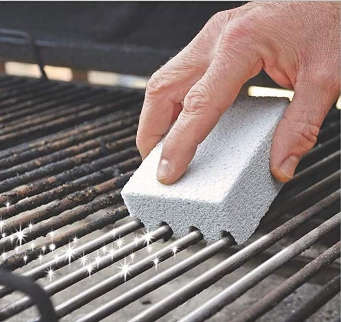 a hand using the scrubber on a dirty grill grate