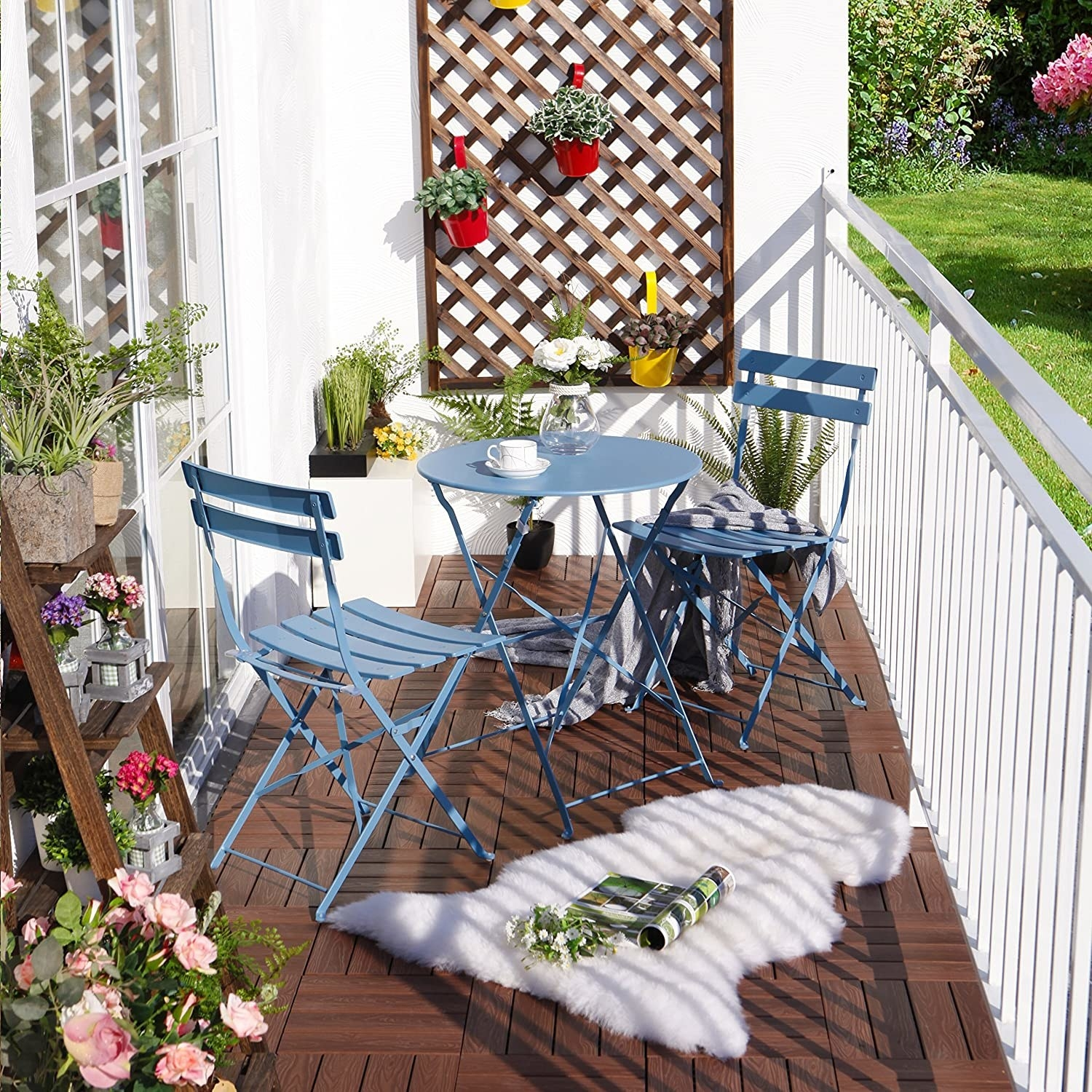 the light blue bistro table and chair set on a small balcony with flowers and plants