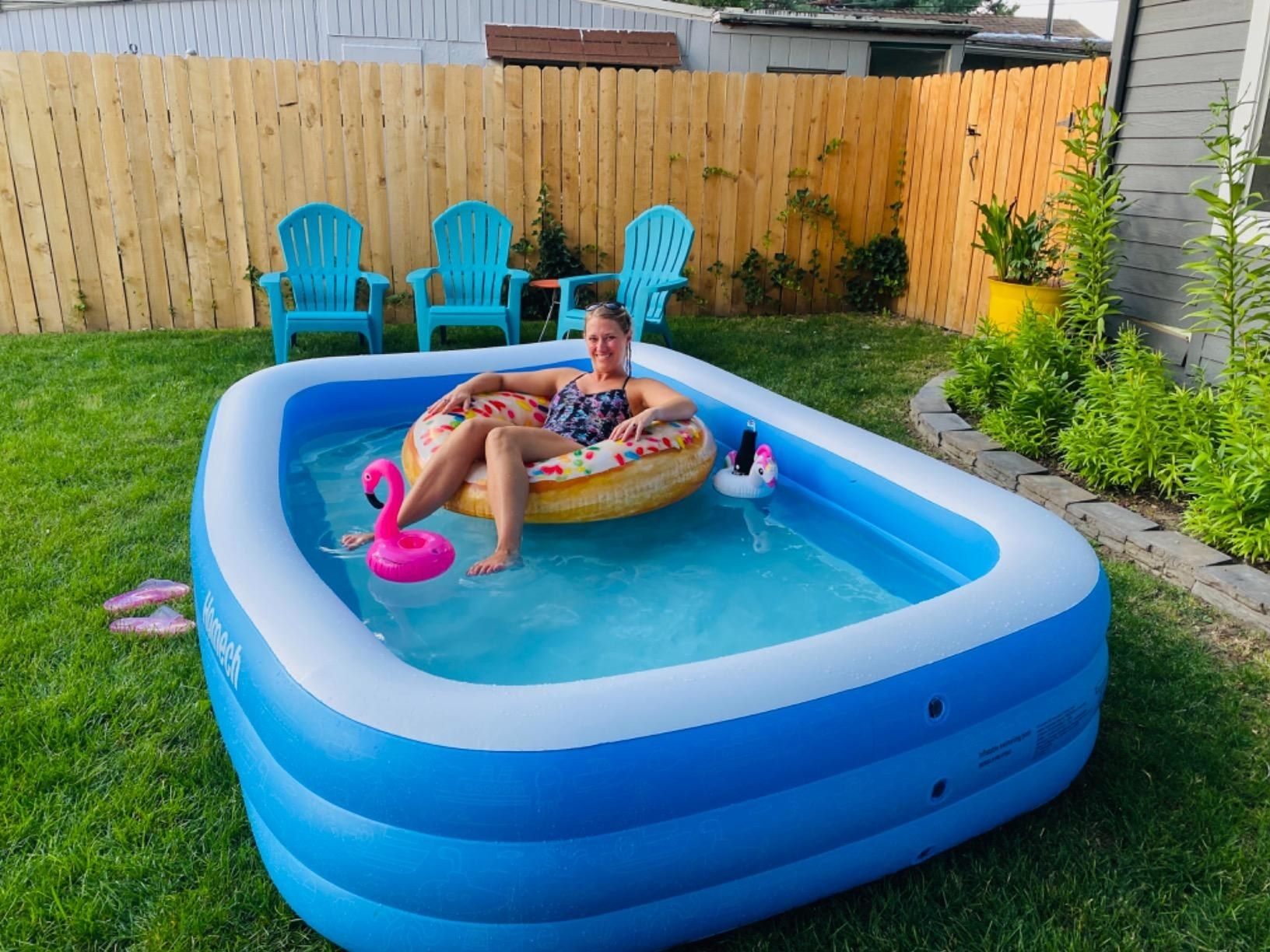 image of reviewer floating on a donut floaty in a full homech inflatable pool