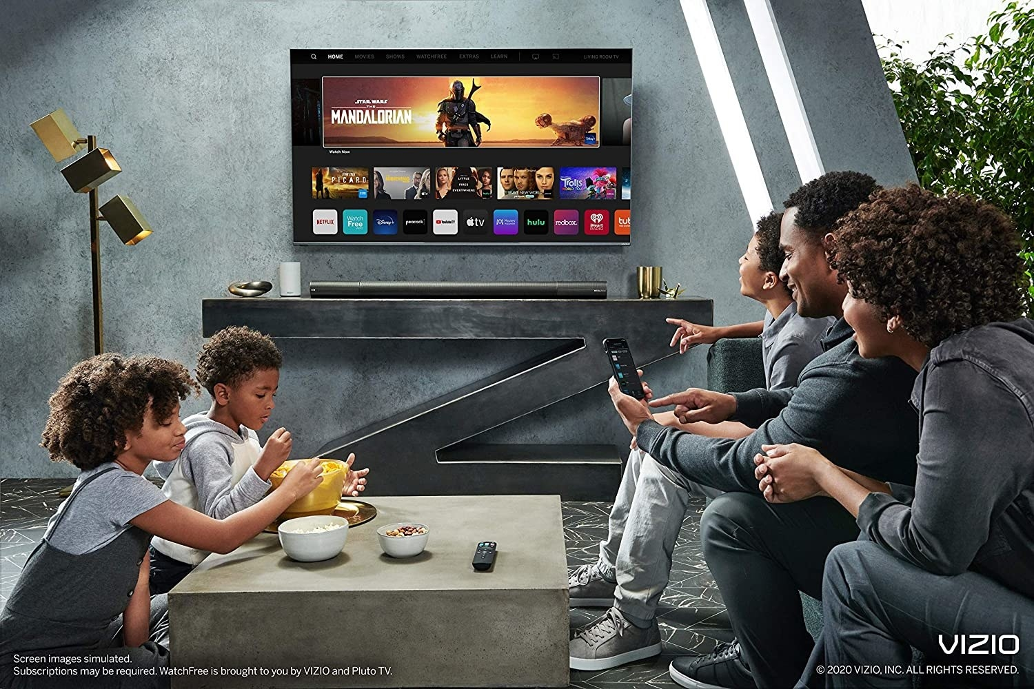 a family eating snacks around the tv