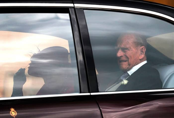 Prince Philip and Queen Elizabeth riding in the back of the car