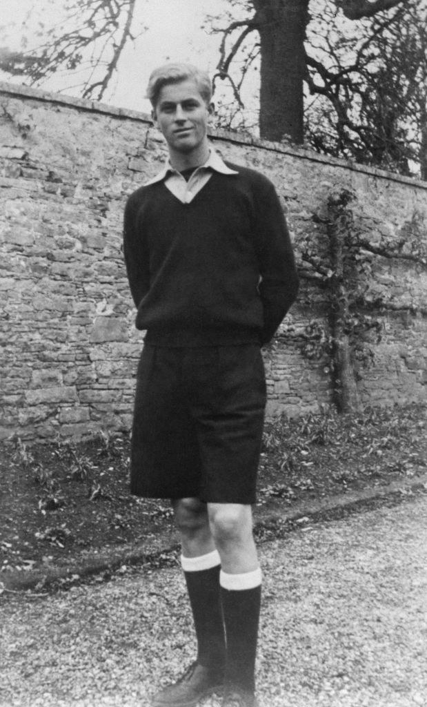Prince Philip standing outside and wearing a sweater, shorts, and knee-high socks