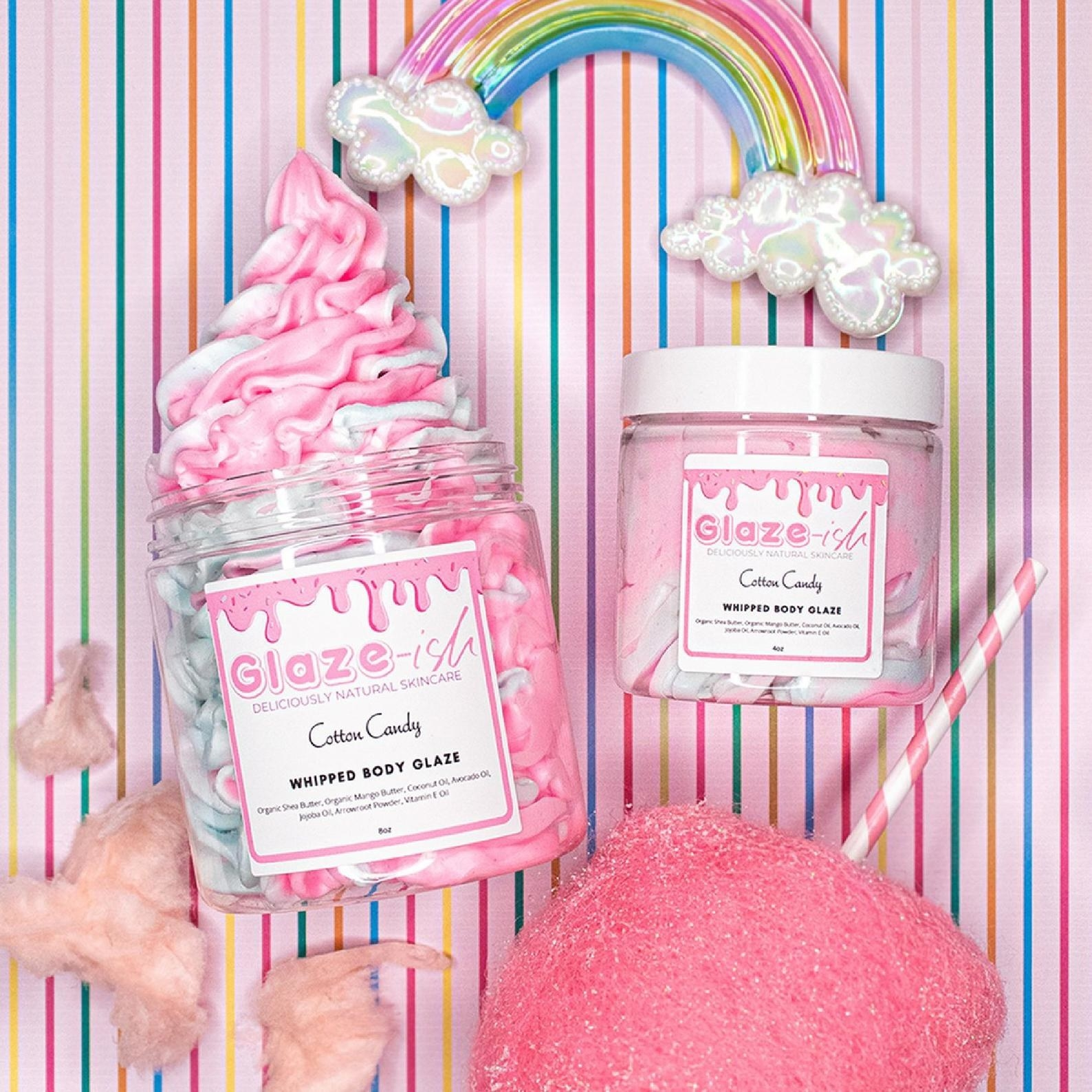 a pink and white swirled body butter in a jar next to candy and rainbows