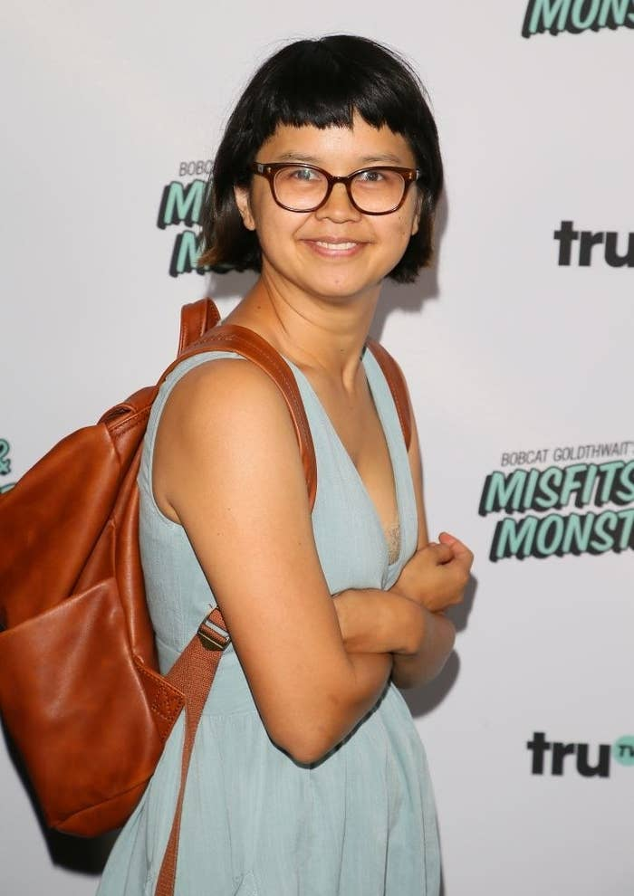 Charlyne posing on a red carpet while wearing a leather-style backpack