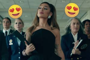 Ariana Grande walks down a hall flanked by a female entourage during the music video of