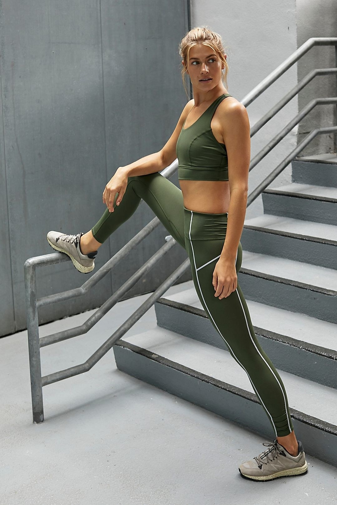 Model wearing olive green leggings with white piping