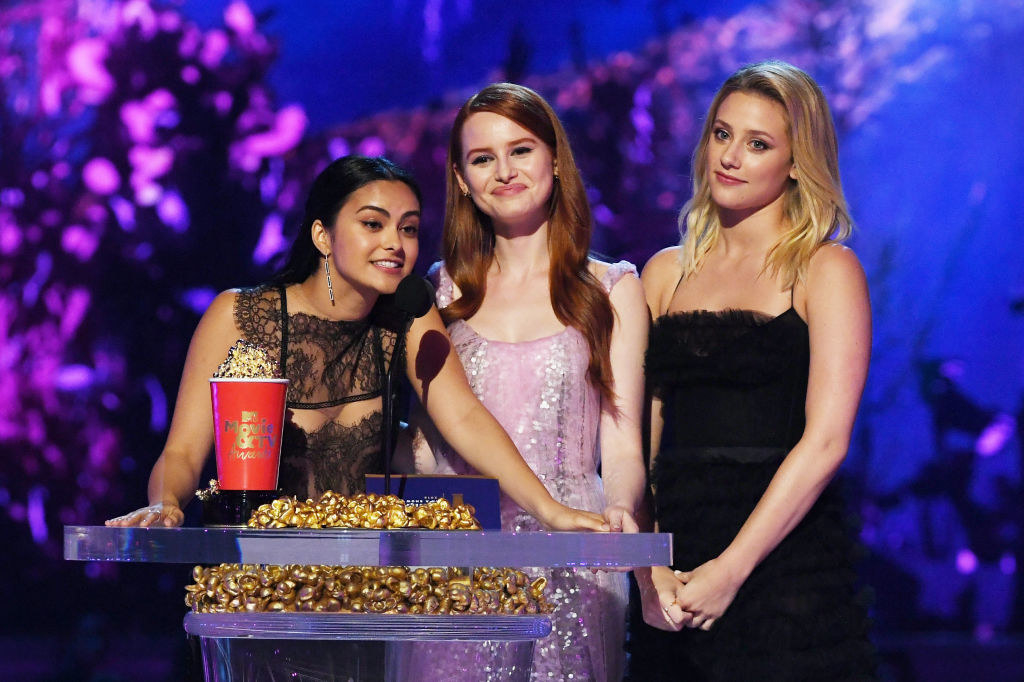 (L-R) Actors Camila Mendes, Madelaine Petsch, and Lili Reinhart speak onstage during the 2018 MTV Movie And TV Awards