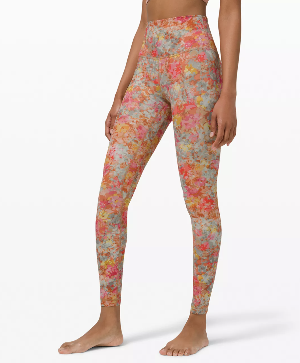 model wearing the full-length leggings in peach, yellow, and red floral print