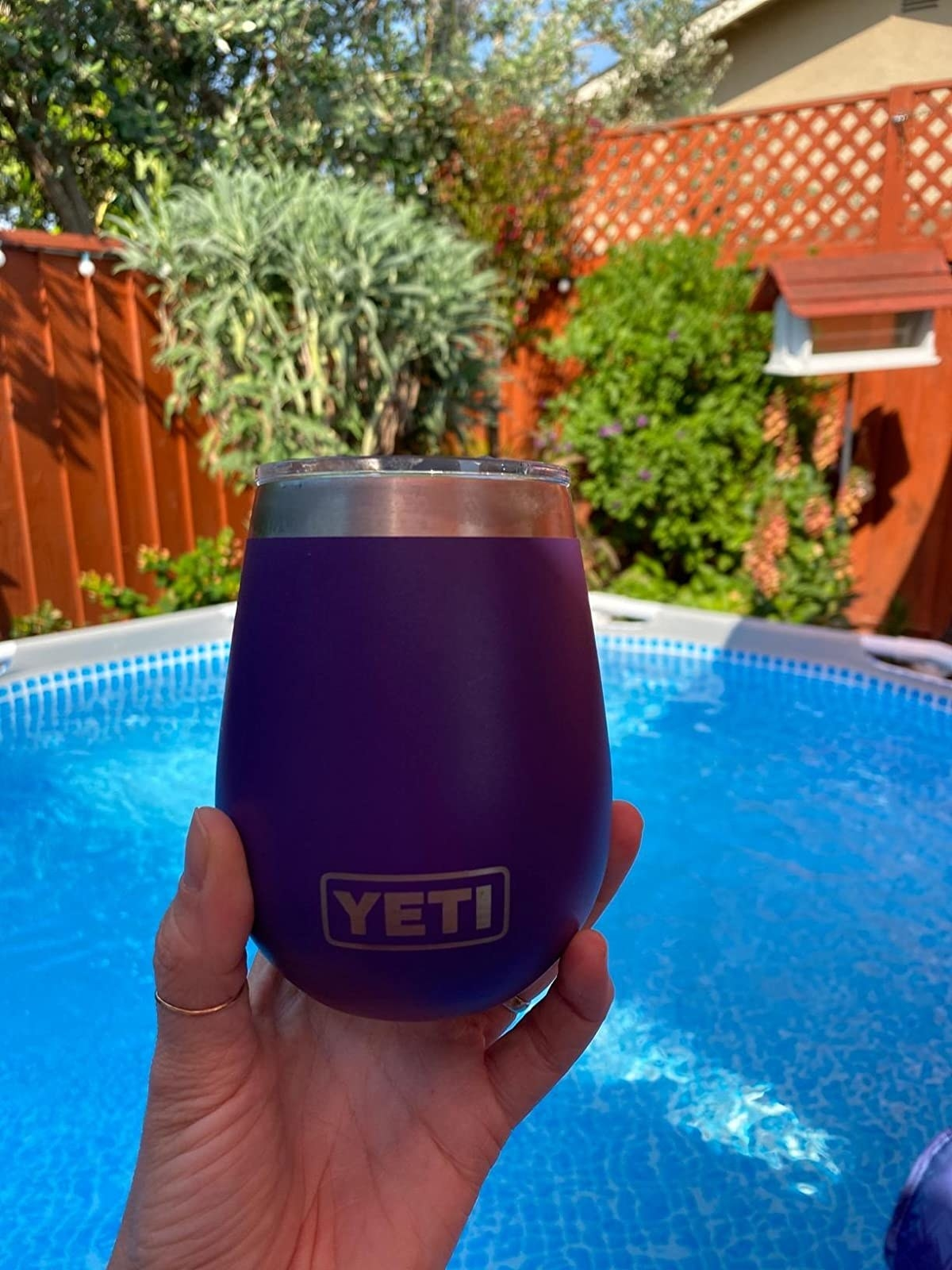 hand holding a stemless wine glass drink container in front of a pool