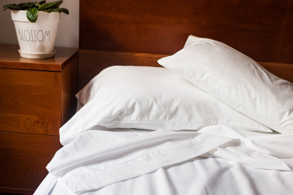 The sheets looking slept in on a bed