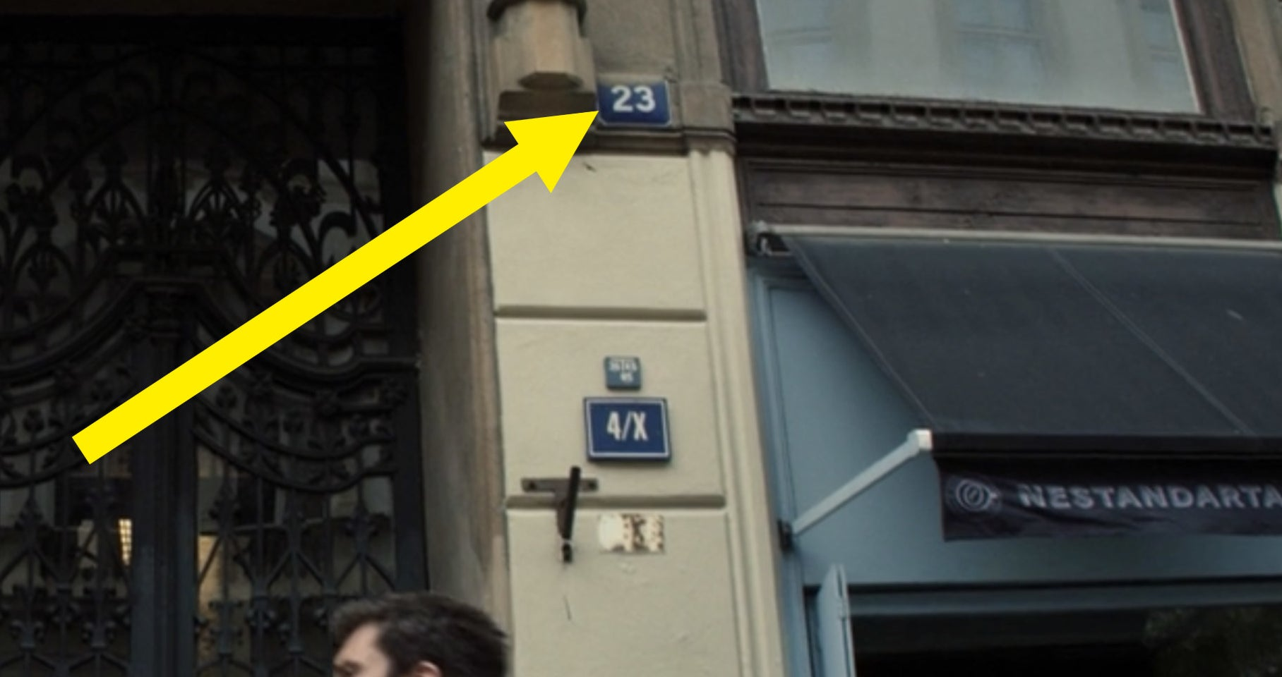 """A yellow arrow pointing to """"23"""" on a building"""